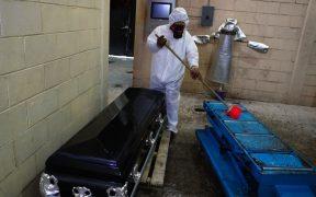Un trabajador limpia con desinfectante una base para colocar cadáveres para cremación en Ecatepec. Foto: AP