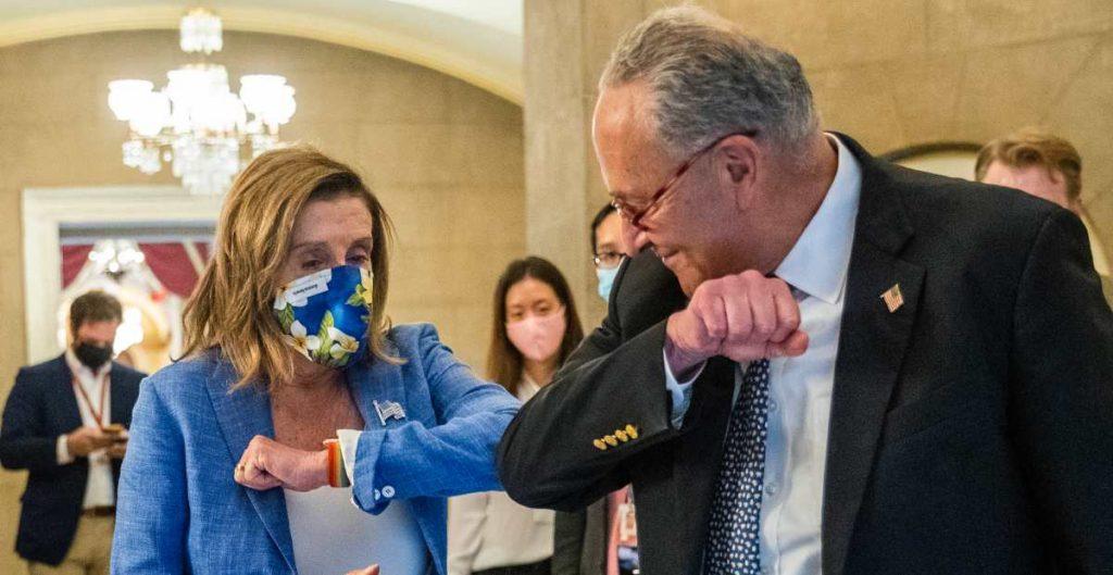 La presidenta de la Cámara de Representantes, Nancy Pelosi, de California, le da un golpe en el codo al líder de la minoría del Senado, Chuck Schumer, de Nueva York.