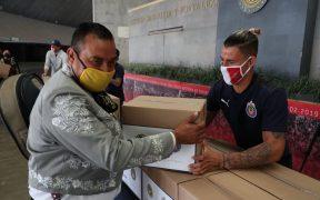 Cristan Calderón, de Chivas, entrega una despensa en el Estadio Akron de Guadalajara. (Foto: @Chivas)