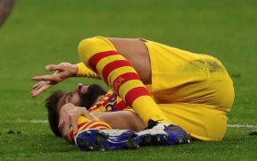 Gerard Piqué se duele tras lesionarse la rodilla derecha ante el Atlético de Madrid.
