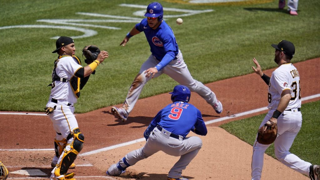 Báez logró escapar a primera base, mientras Contreras se acerca a anotar. (Foto: AP).
