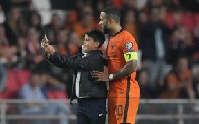 Depay accedió a tomarse una 'selfie' en pleno partido con un joven que saltó a la cancha. (Foto: AP).